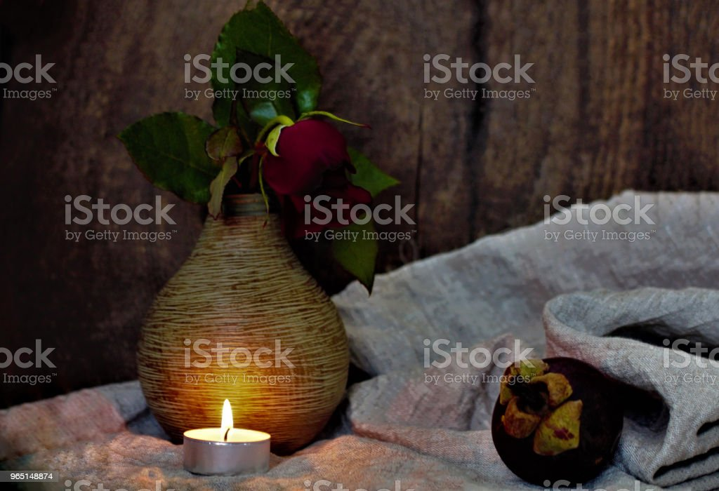Still life with a beautiful flower. Red rose in a vase. On the table is a rough fabric and exotic fruits. Lifestyle wabi sabi. royalty-free stock photo
