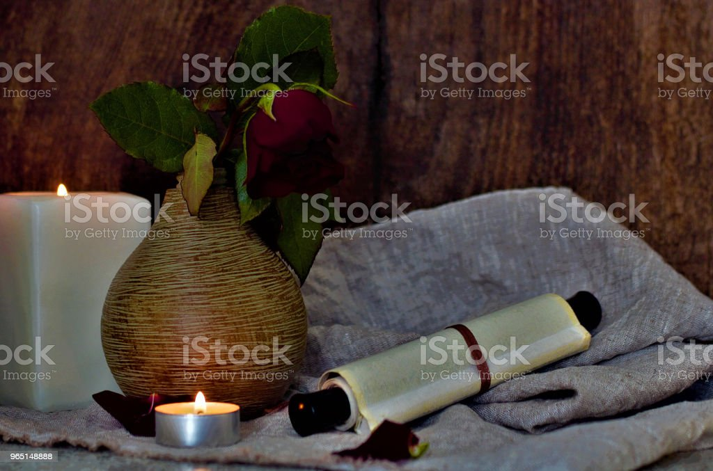 Still life with a beautiful flower. Red rose in a vase. On the table is a coarse cloth and a scroll. Lifestyle wabi sabi. zbiór zdjęć royalty-free