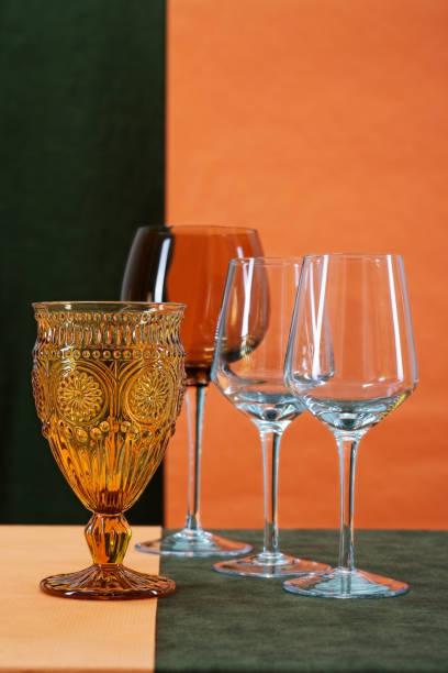 stillleben mit einem braunen glas und gläser für wein auf dem tisch auf einem bunten hintergrund platziert - herbst hochzeitseinladungen stock-fotos und bilder