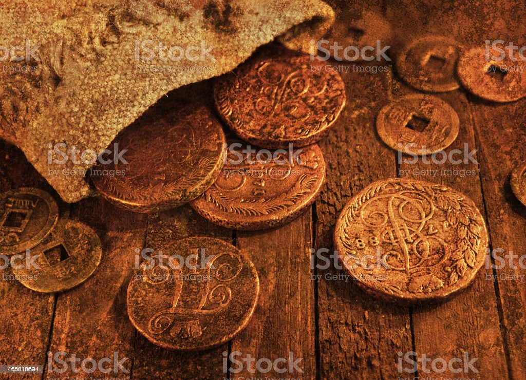 Still life with ancient coins, grunge texture effect Close up of old ancient coins on wooden background in candle light, with grunge texture effect. Source file of texture included 2015 Stock Photo