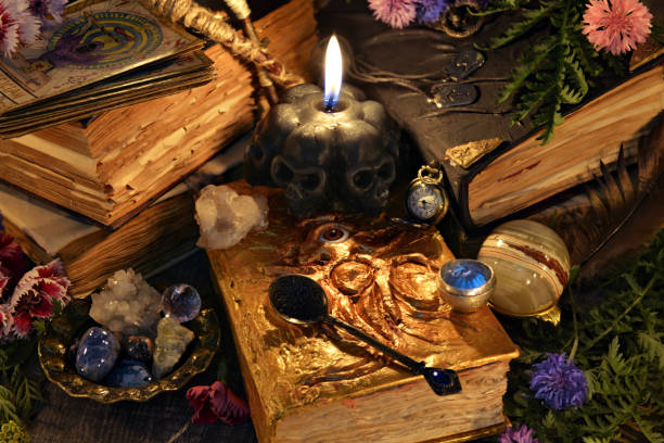 Still life with antique witch book, black candle and ritual objects stock photo