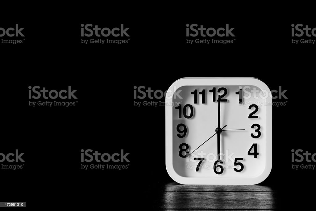 Still life with black and white clock on wood table stock photo