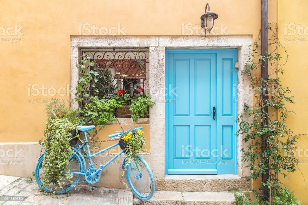 Still life with blue bicycle at door and window of a house. royalty-free stock photo