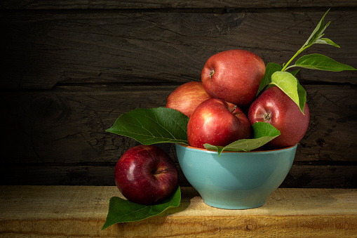 Blue bowl with apples. Still life with ripe apples on wooden background in rustic style. Beautiful background with harvest of red apples.
