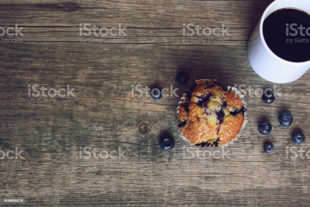 Still life with blueberry muffin, coffee, and blueberries over rustic wooden background, copy space stock photo