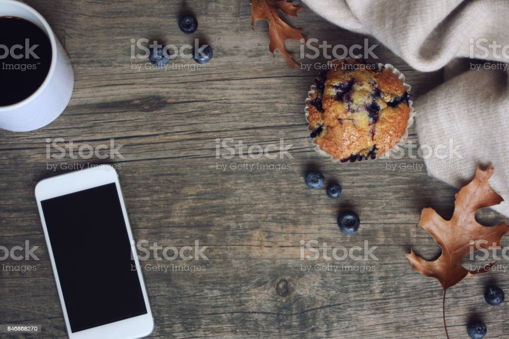 Still life with blueberry muffin, coffee, mobile phone, blanket, leaves and blueberries over rustic wooden background, copy space stock photo