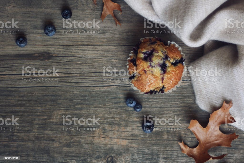 Still life with blueberry muffin, warm blanket, leaves and blueberries over rustic wooden background shot from directly above stock photo