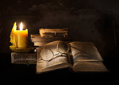 Still life with old books, old glasses and wax candle.Wax candle is drip.Lighted with flashlight.