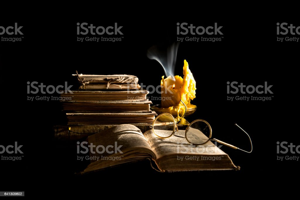 Still life with book, candle and glasses stock photo