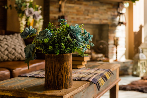 Still life with bouquet in a ceramic , wooden vase on wooden table desk. House or restaurant , resting area design with fireplace.a bouquet of green plant branches.Interior design of room with  flowers.Ornamental plants cones hops in a  vase. Fresh green