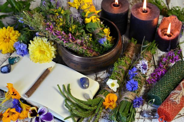 Still life with bowl of herbs, candles and old book on witch table. stock photo