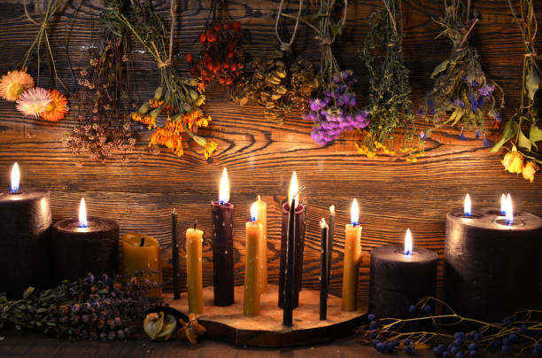 Still life with burning candles and dry herbs on witch table. stock photo