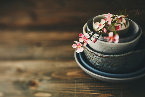 Still life with ceramic bowls and blossoms on rustic wood table