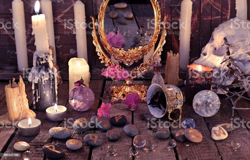 靜物與燃燒的蠟燭和石符文的咖啡杯 免版稅 stock photo