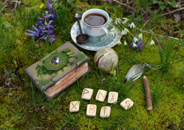 Still life with crafted witch diary, tea set, runes and crystals in the garden. stock photo
