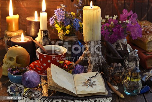 811119304 istock photo Still life with cup of tea, burning candles, open diary with copy space and crystal on witch table. 1249943716