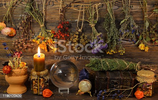 Still life with dry herbs, crystal ball, bottle and burning candle on witch table. Esoteric, wicca and occult background, fortune telling and divination ritual, mystic concept