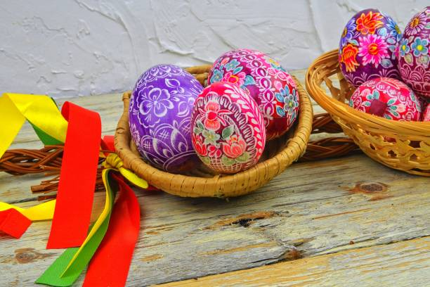 Still life with Easter eggs. Decorated Easter eggs lay in a wicker basket on a white wooden background. Easter eggs, decorated with traditional folk designs - east Europe, Czech Republic. stock photo