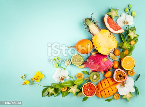 Still life with fresh assorted exotic fruits and flowers on blue background. Concept of healthy eating with fruits and tropical flowers. Top view.