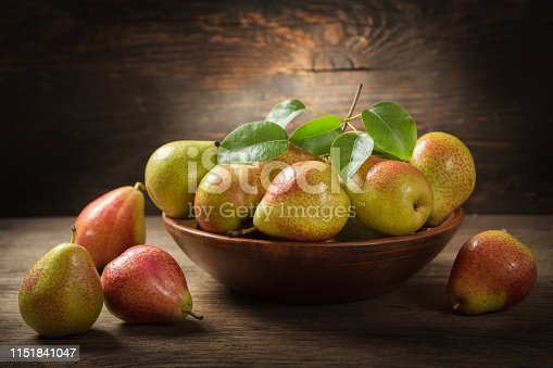 still life with fresh pears with leaves in a bowl on a wooden table