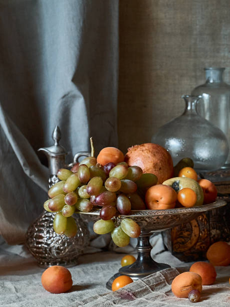 Still life with fruits A classic still-life in the Dutch old masters painting style with  fruits on a silver, platter, silver carafe and glass botles still life stock pictures, royalty-free photos & images