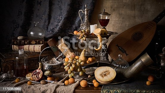 A classic still-life in the Dutch old masters painting style with  fruits on a silver, platter, silver carafe. old books , glass of wine, hunting horn and guitar lute .