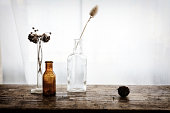 Still life with glass bottles and dried meadow flowers