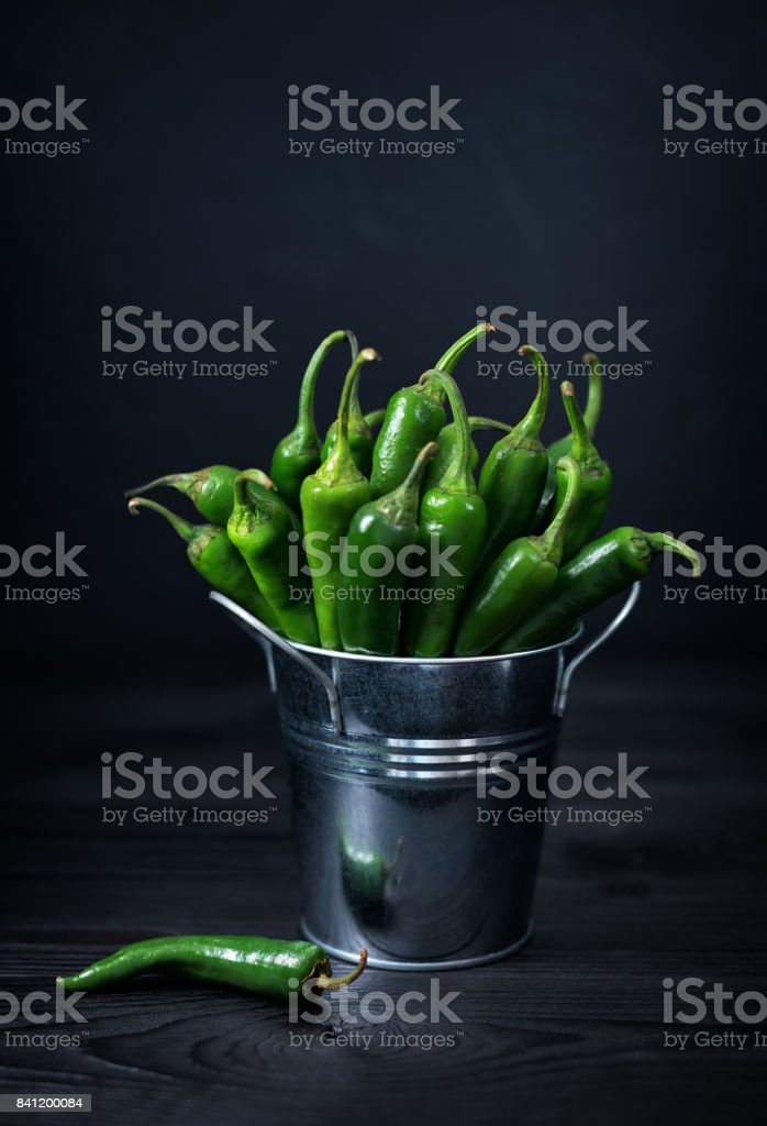 Still life with green chili pepper on wooden table in moon mystic light stock photo