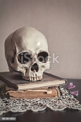 1176385551istockphoto Still life with human skull and old vintage book on wood 954844834
