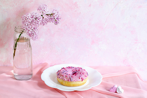 Still life with lilac twig, donut on figured plate and small heart shaped marshmallows on pink fabric on pink background.