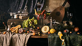 A classic still-life in the Dutch old masters painting style with lobster, fruits on a silver, platter, silver carafe. old books , glass of wine, hunting horn and guitar lute .