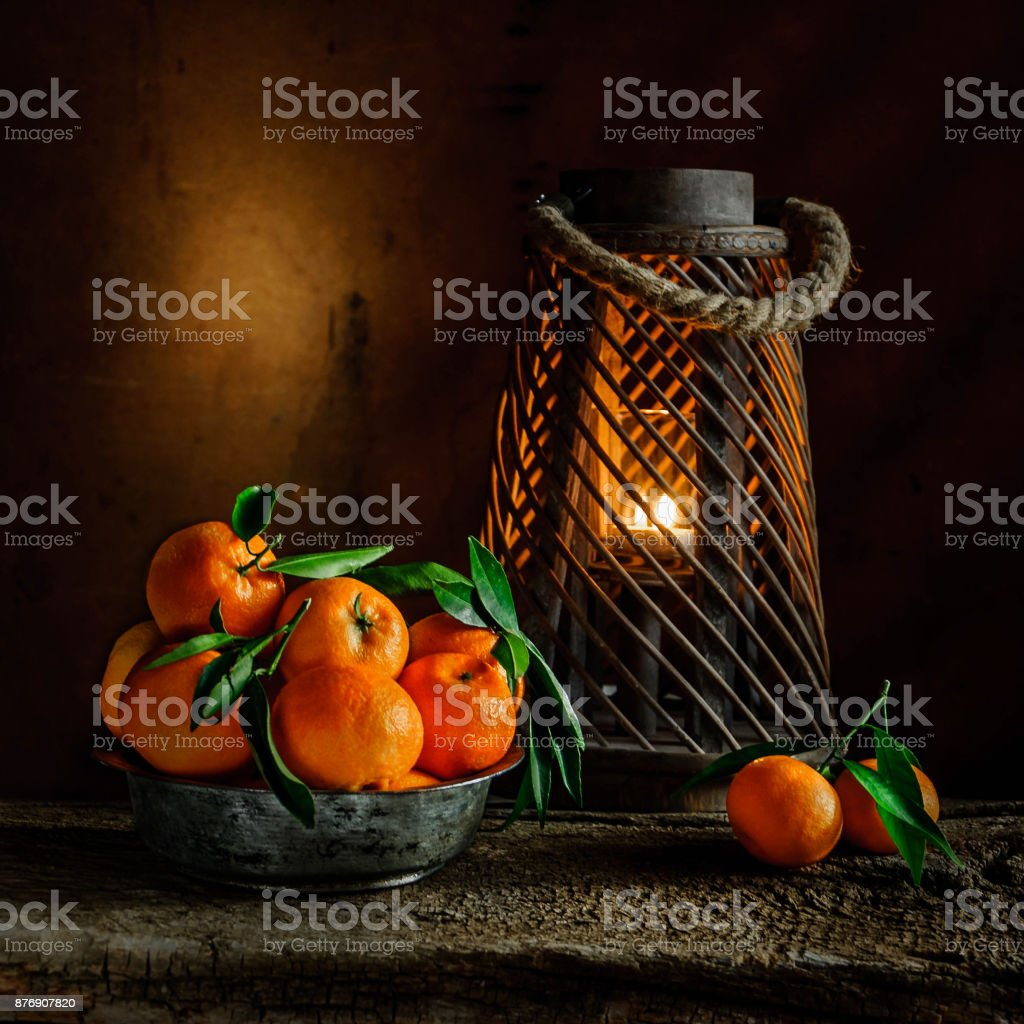 still life with mandarins in the tin bowl and candlelight on wooden background stock photo