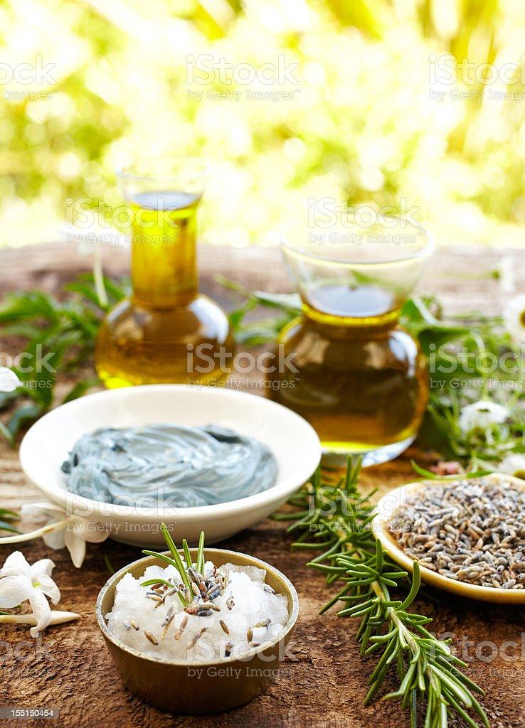 Still life with massage oil, chamomile mud mask, rosemary, salt royalty-free stock photo