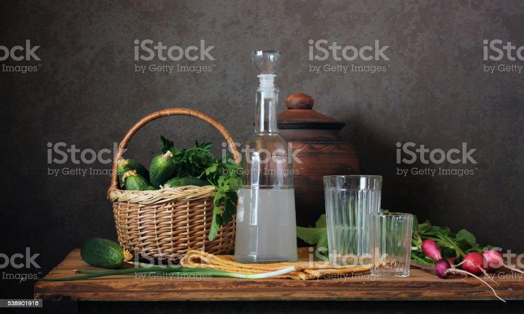 Still life with moonshine, radish and fresh cucumbers. stock photo