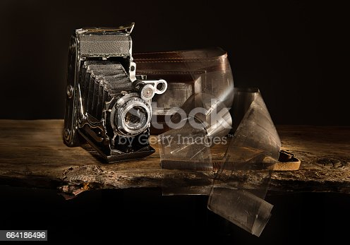 Old analogue photo camera Moskva-4 with films on the old plank. In background photo camera's carrying bag.Lighted with flashlight.