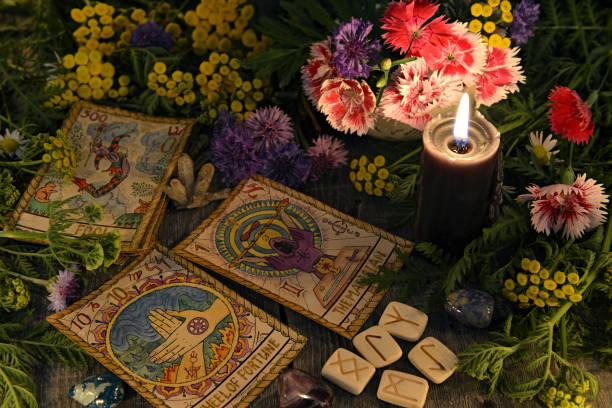 Still life with old tarot cards, black candle, runes, healing herbs and flowers stock photo