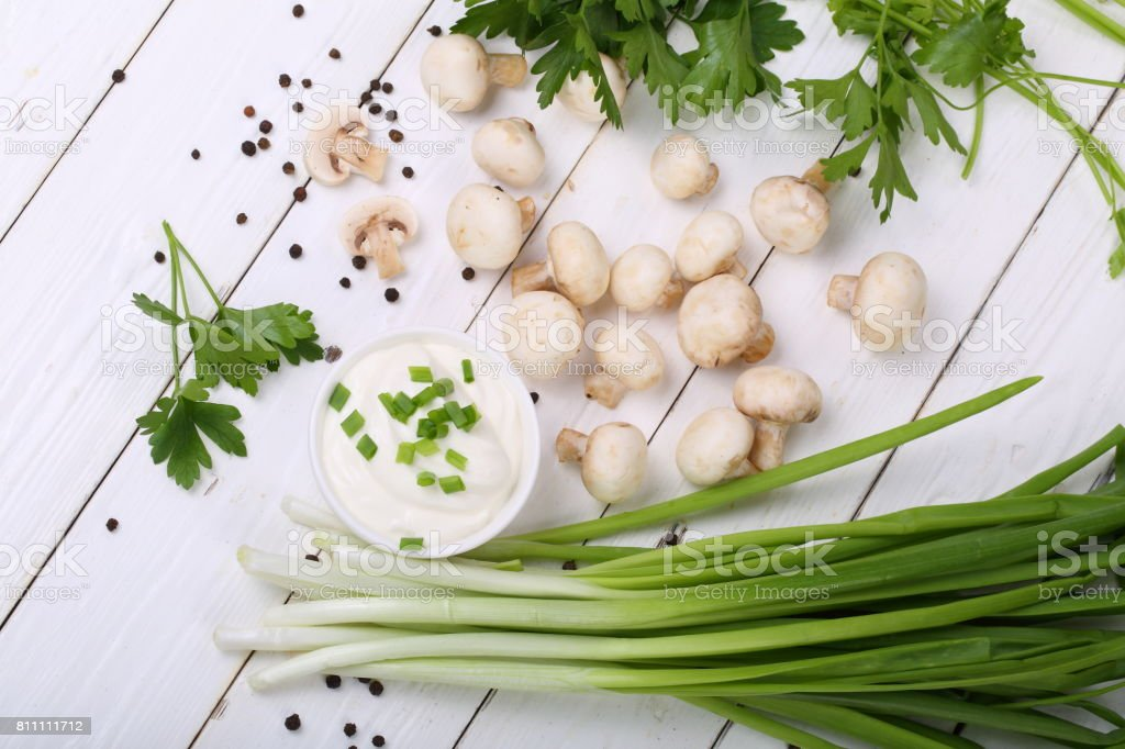 Still life with onions and champignons on a white wooden background stock photo