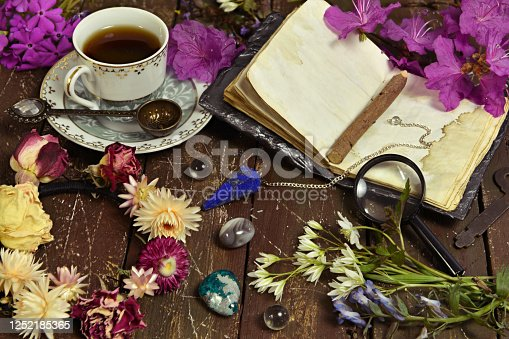 811119304 istock photo Still life with open diary book, cup of coffee and crystal stone on witch table. 1252185365