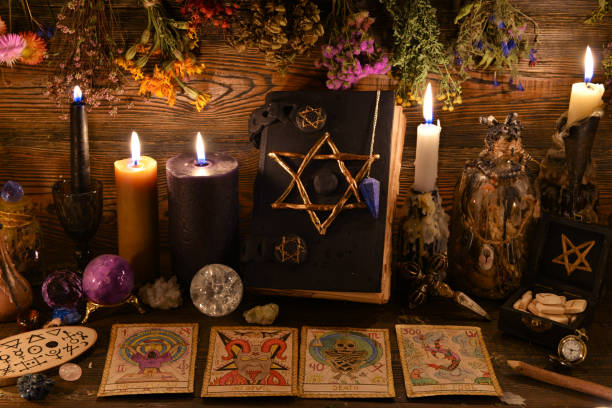 Still life with pentagram book, burning candle, crystal gemstone and tarot cards on witch table. stock photo