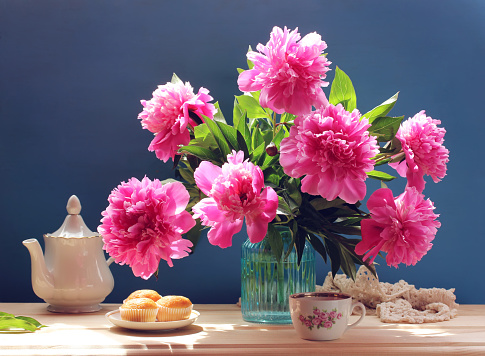 Still life with peonies, cakes and teapot.