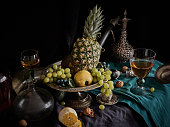 A classic still-life in the Dutch old masters painting style with pineapple, fruits on a silver, platter, silver carafe with dragon ornament, glass of wine,