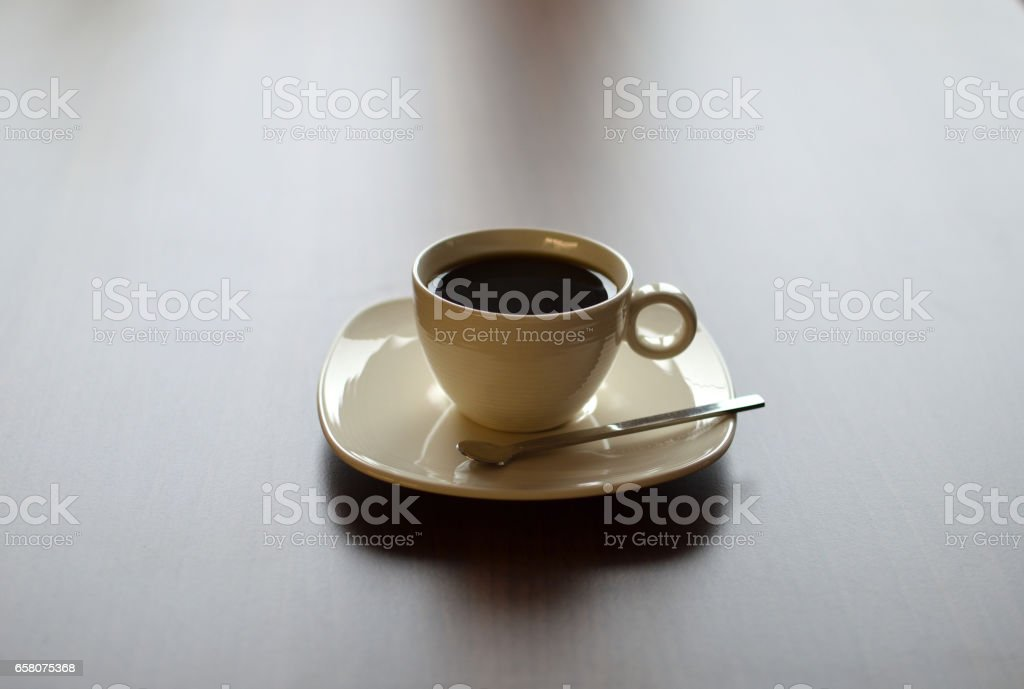 Still life with porcelain coffee cup on saucer with spoon on wooden table royalty-free stock photo