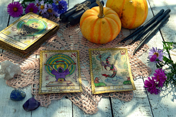 Still life with pumpkins, tarot cards and black candles on old napkin with embroidery stock photo