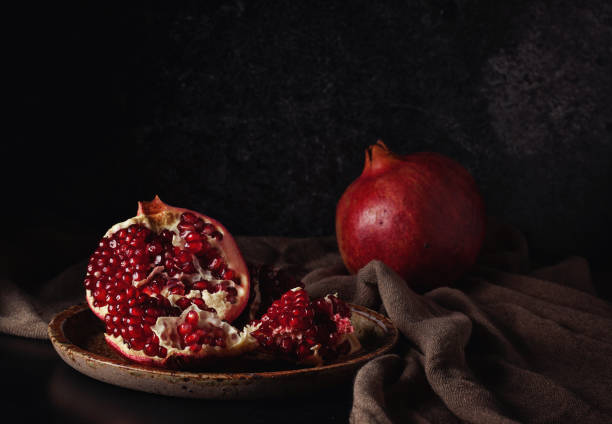 still life with red juicy pomegranates - nature morte photos et images de collection