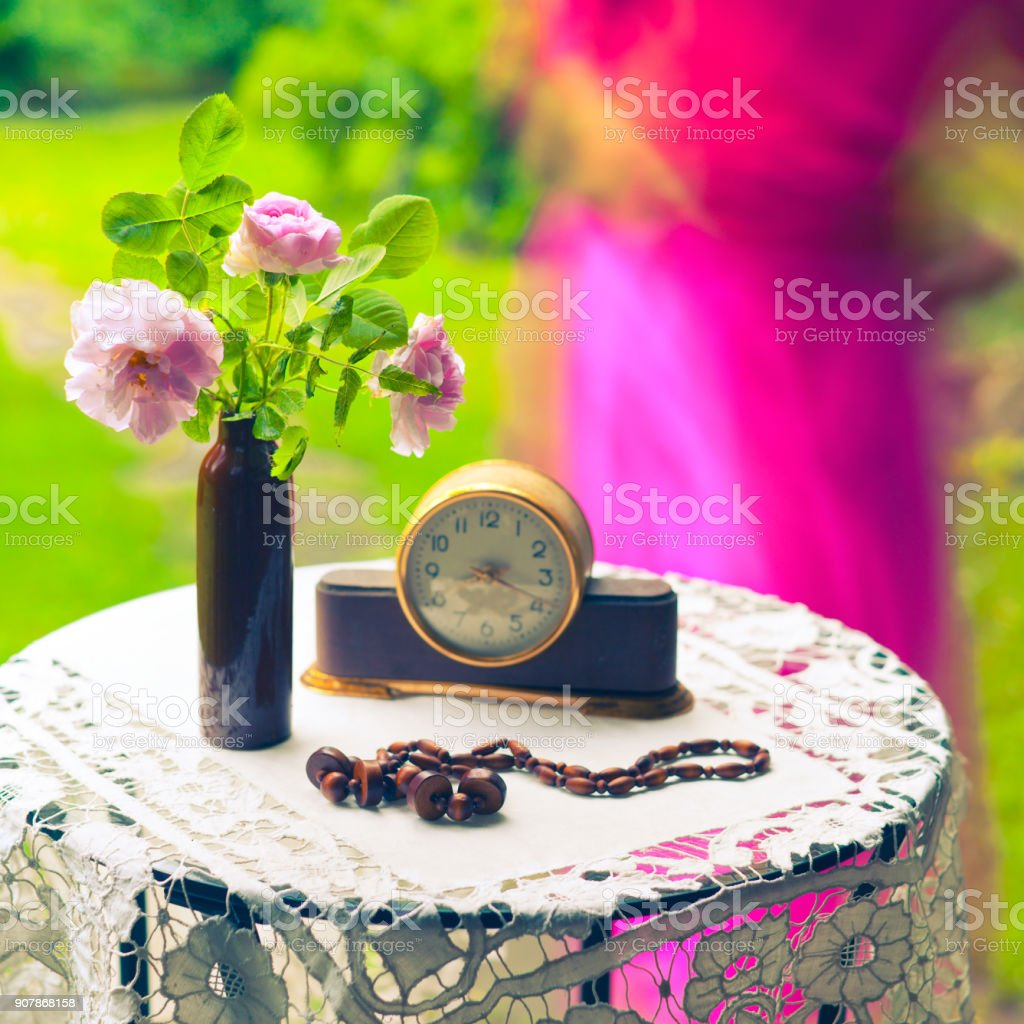 Still life with roses and vintage table clock stock photo