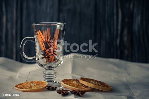 istock still life with spices. cinnamon and star anise in a transparent glass cup with dried grapefruit slices on paper and a dark wooden background. side view 1153723962