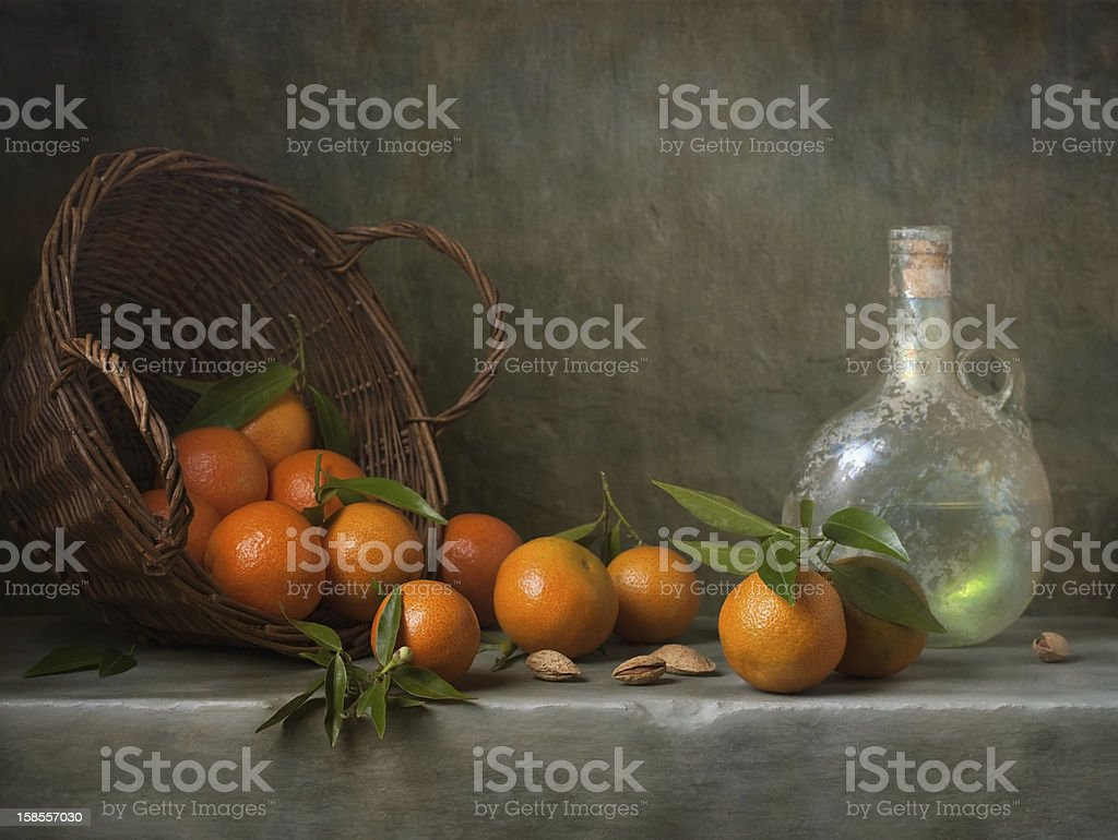Still life with tangerines and antique bottle stock photo
