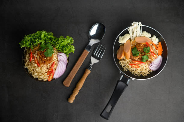 Still life with the noodles in a frying pan, fork, and spoon on the black cement floor. stock photo