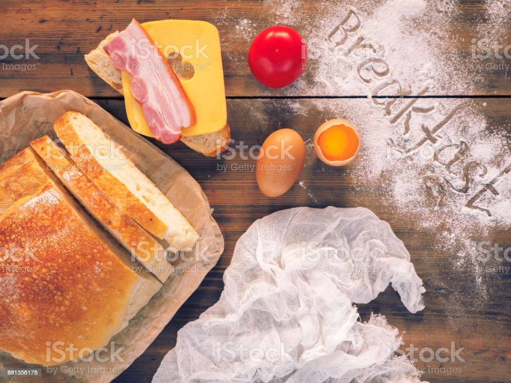 Still life with the word Breakfast, on the wooden table, top view. Fresh, sliced bread with a slice of ham and cheese, egg and tomato. A sandwich for Breakfast, background for article about food stock photo