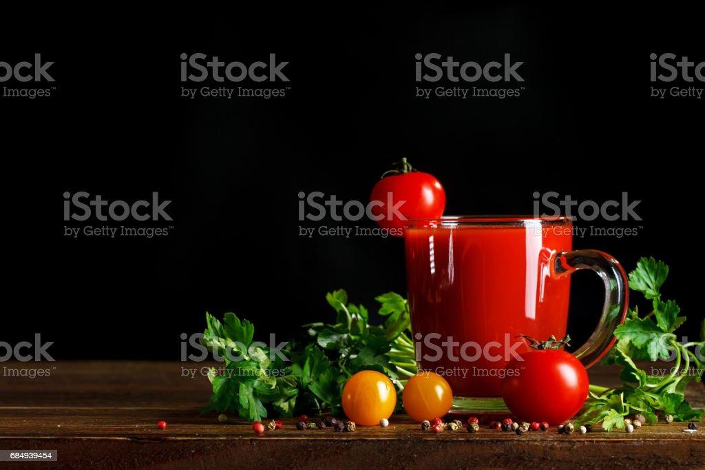 Stillleben mit Tomaten, Petersilie, Knoblauch und Tomaten Saft auf Holzbrettern. Auf einem schwarzen Hintergrund. Lizenzfreies stock-foto